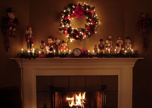 Christmas wreath and fairy lights above a log burning fireplace