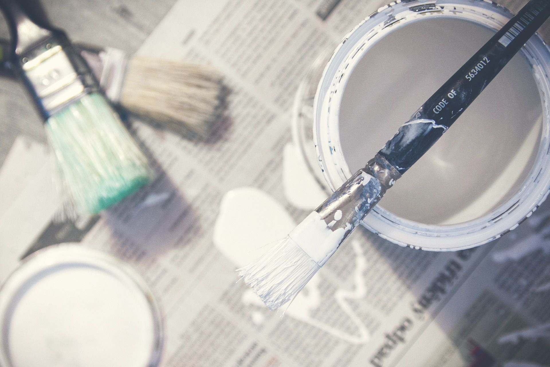 paint brushes and paint on newspaper.